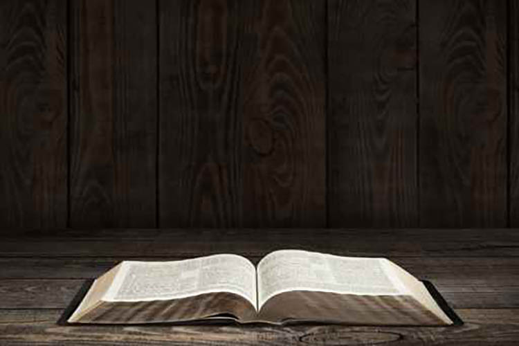 Bible. Image of an old Holy Bible on wooden background in a dark